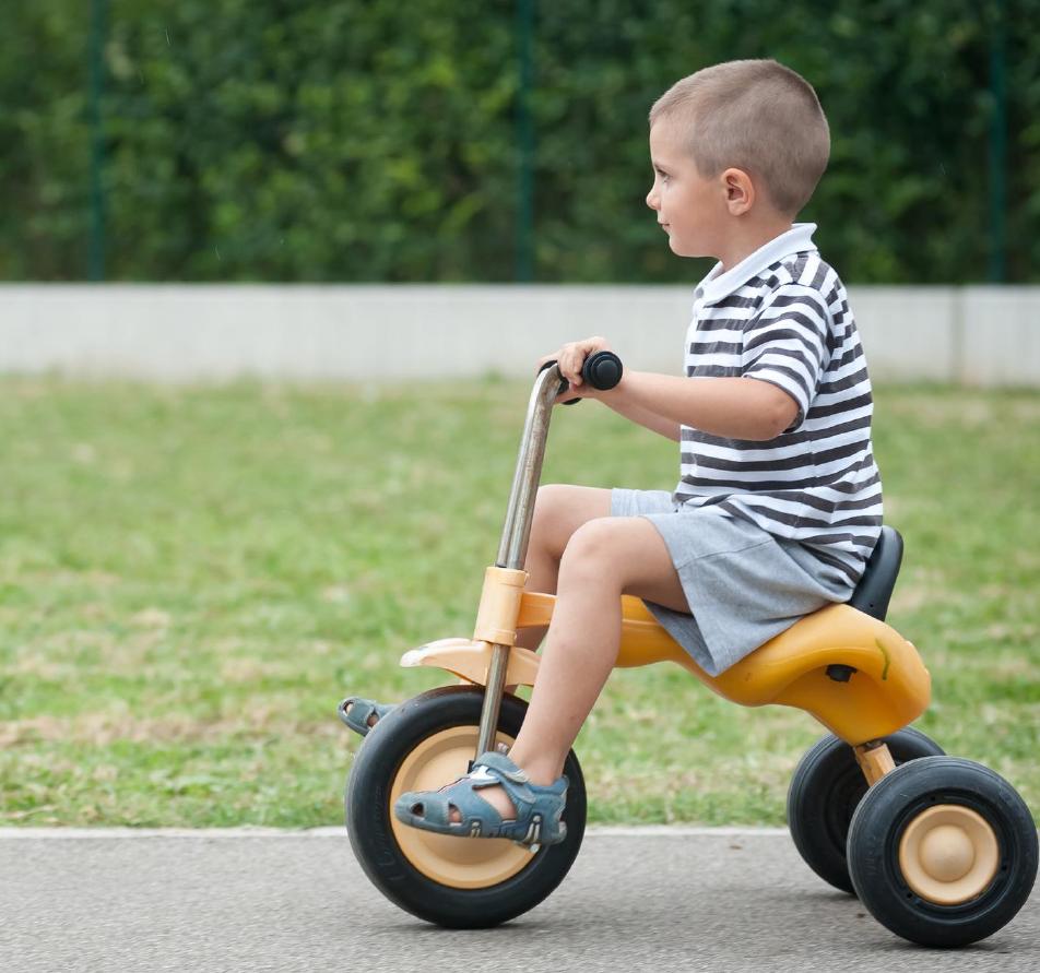 Criança andando de triciclo